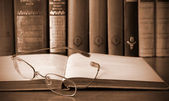 Vintage photo of book and glasses in library — Stock Photo