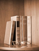 Vintage photo of old books and glasses on a shelf — Stock Photo