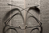 Reading glasses on an open book — Stock Photo