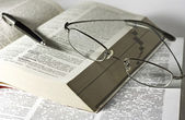 Opened books, glasses and pen — Stock Photo