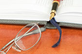 Pen, glasses and notebook — Stock Photo