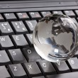 Globe on laptop keyboard — Stock Photo