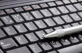 Black laptop and silver pen — Stockfoto