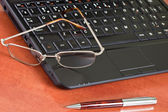 Laptop, glasses and pen — Stock Photo