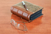 Old book with reading glasses and pen — Stock Photo