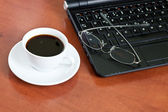 Cup of coffee with a laptop and glasses — Stock Photo