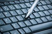 Pen over laptop keyboard — Stock Photo