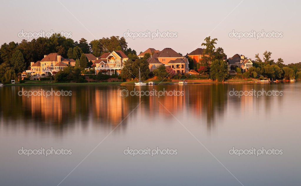 Beautiful scene of houses by the lake surrounded by forests  at sunset time  Stock Photo #9370390