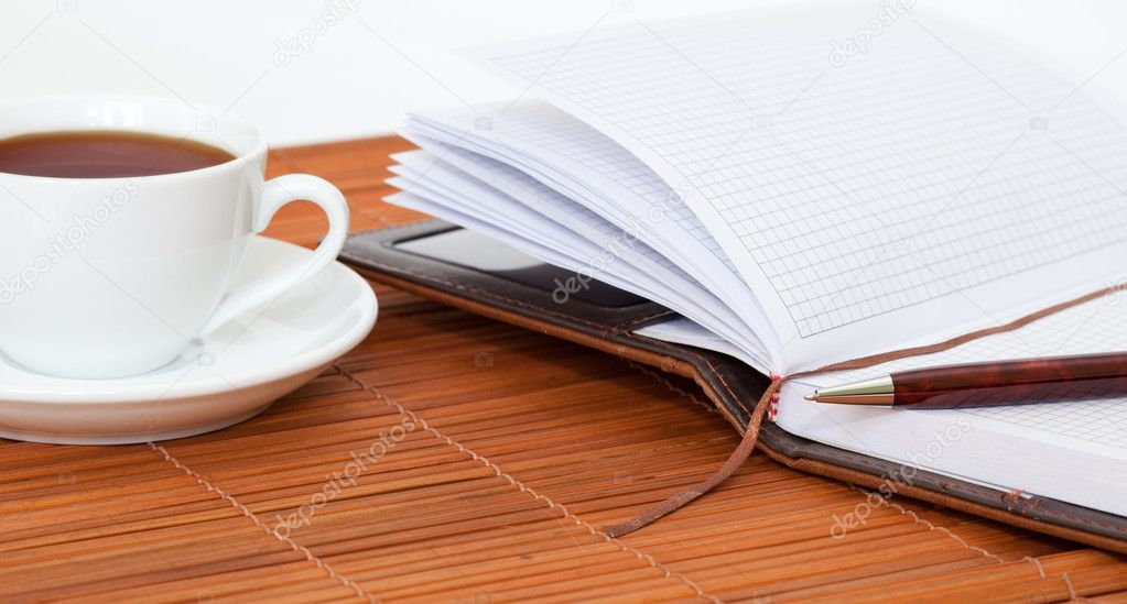 White cup of tea with notebook and pen on table — Stock Photo #9500627