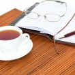 Cup of tea with notebook, glasses and pen — Stock Photo