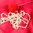Pearl necklace with red heart on red silk — Stock Photo