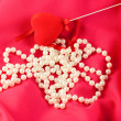 Pearl necklace with red heart on red silk — Stock Photo #9556354