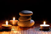 Burning candles and and a stack of pebbles — Stock Photo