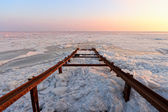 Frozen sea with broken pier at sunset — Stock Photo