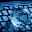 Crystal globe on laptop keyboard — Stock Photo