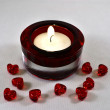 Royalty-Free Stock Photo: A red candle holder with nine small red hearts beside.