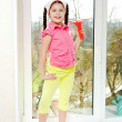 Stock Photo: Girl with squeegee stands on windowsill