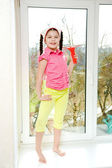 Girl with squeegee stands on a windowsill — Stock Photo