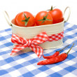 Cherry tomatoes in  bucket with bow and pepers — Stock Photo