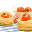 Pasta nest and tomatoes cherry on plaid napkin — Stock Photo