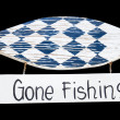 Stock Photo: Wooden gone fishing sign, isolated on black background