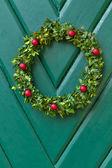 Vánoční věnec pověsit na dřevěné dveře — Stock fotografie