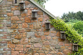 Small insect hotels on a house wall — Stock Photo