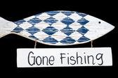Wooden gone fishing sign, isolated on black background — Stock Photo