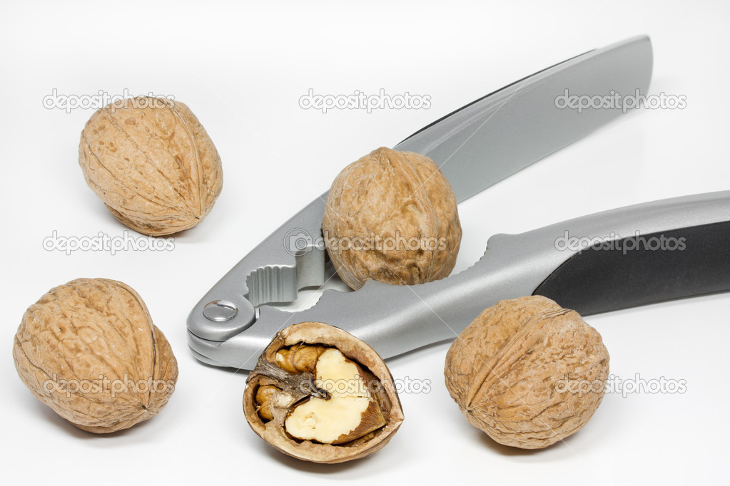 Walnuts with nut cracker on white background — Stock Photo #9175304