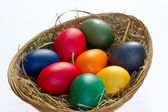 Colored easter eggs in a small basket — Fotografia Stock