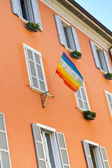Facade of a typical residential building in Italy with peace flag — Stock Photo
