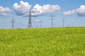 Electrical towers on a meadow in spring time — Stock Photo