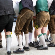 Young guys in Lederhosen erecting a maypole — Stock Photo