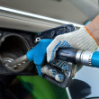 Close-up of a mens hand refilling the car with a gas pump — Stock Photo #9245136