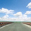 Asphalt road with a fence against the blue sky — Stock Photo