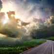 The road through the meadow and the stormy skies — Stock Photo #9245548