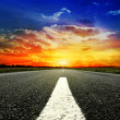 Road vanishing to the horizon under sun rays coming down trough the dramatic stormy clouds — Stock Photo