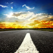 Road vanishing to the horizon under sun rays coming down trough the dramatic stormy clouds — Stock Photo #9245591