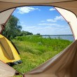 View looking out of door of sun-filled tent upon great outdoors — Photo