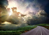 The road through the meadow and the stormy skies — Foto Stock