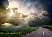 公路穿过草地和狂风暴雨的天空 — 图库照片