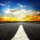 Route en voie de disparition à l'horizon sous les rayons de soleil qui descendait creux des nuages orageux dramatiques — Photo