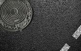 Sphalt en het luik. close-up — Stockfoto
