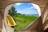 View looking out of door of sun-filled tent upon great outdoors — Stock Photo