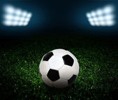 Soccer ball on the field of stadium with light — Stock Photo