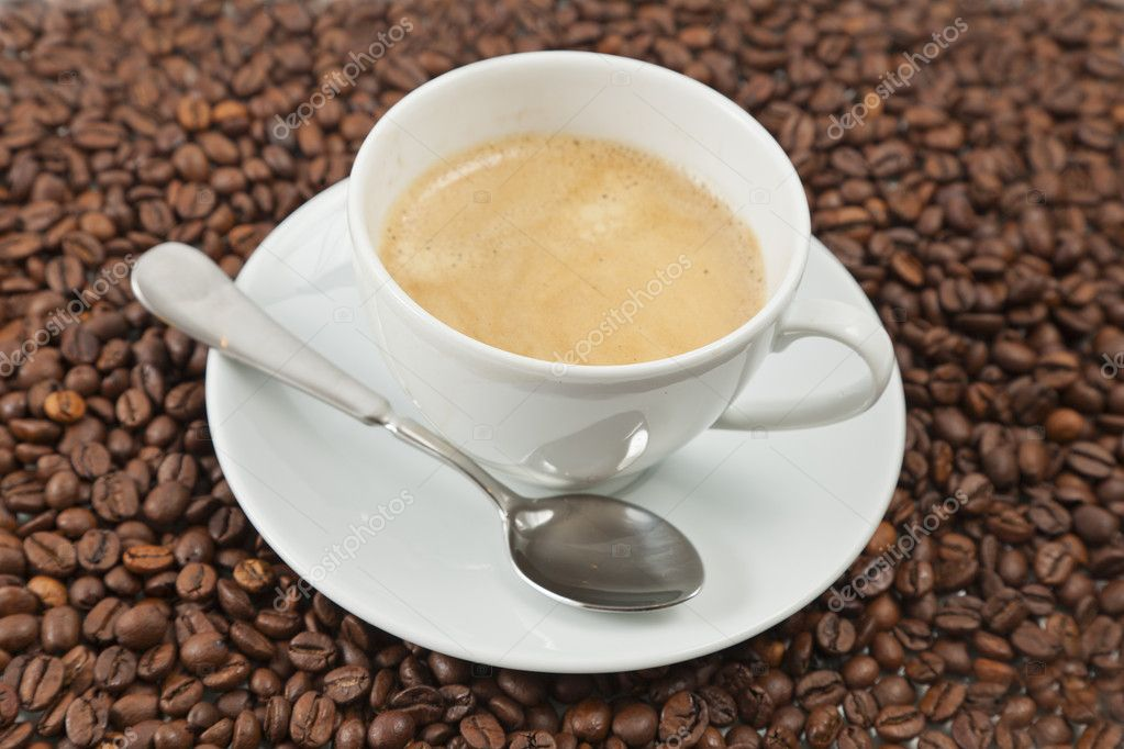 Cup of coffee sitting in a bed of coffee beans — Stock Photo #9734705