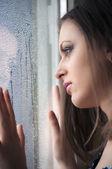 Beautiful girl watching through a wet window — Stock Photo