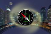 The compass against a night panorama of a city — Stock Photo