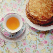 Cup with tea and pancakes — Stock Photo