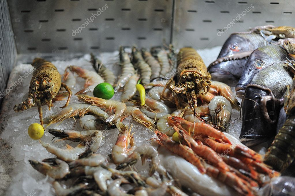 On a counter in ice shrimps, fish, lobsters lie, — Stock Photo #9595513
